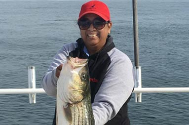 A woman smiles while holding up a striped bass.