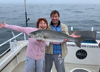 A man and woman proudly smile for the camera and hold up a striped bass.