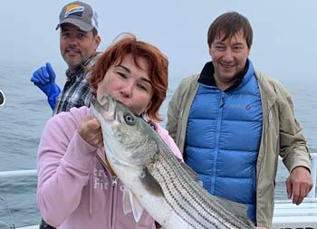 A woman with short red hair kisses the striped bass she caught as a man behind her smiles and looks on.