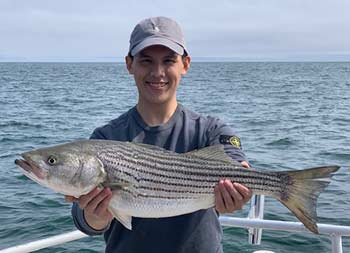 A man smiling and holding up the striped bass he caught.