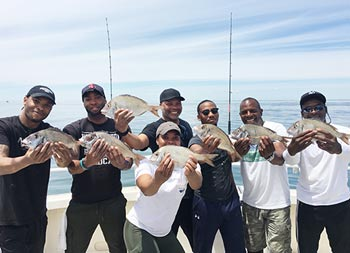 On a sunny day, a group of 6 men and 1 woman each hold up the scup/porgy they caught.