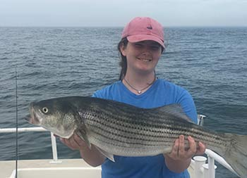 On an overcast day, a teenage smiles and holds up the striped bass she caught .