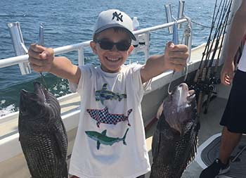 A young boy wearing sunglasses holds up a sea bass in each hand.
