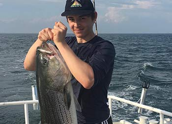 A young man proudly holds up the striped bass he caught