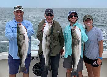 A man with his father and two young adult children, a boy and girl, each hold up a striped bass and smile for the camera.