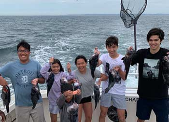 A mix of six young, adolescent and teenage boys and girls smile and hold up the sea bass they caught.