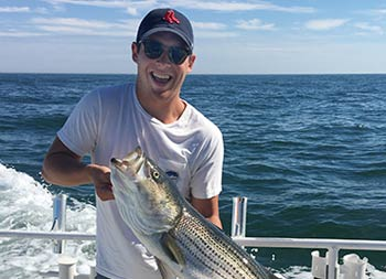 With the blue sky and ocean behind him, a man wearing a baseball cap and sunglasses holds up the striped bass he caught and smiles.