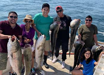 A family of six smile for the camera as they hold up 7 striped bass