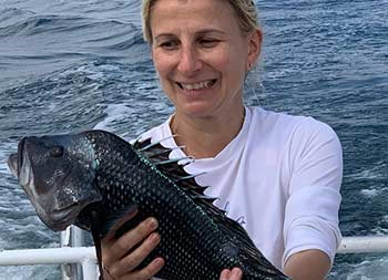 A woman looks at the sea bass she caught as she holds it up for the camera.