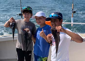 Three young boys each hold up sea bass and give thumbs up/peace sign.