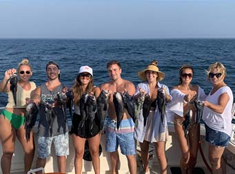 A group of 7 men and women hold up 2 sea bass each.
