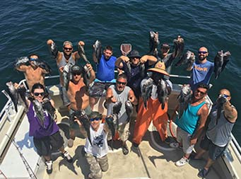 View from atop the boat of thirteen men, including first mate, Gil, looing up at the camera, each holding 2 sea bass.