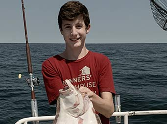 A young man wearing a dark red tshirt holds up the fluke he caught .