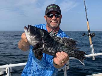 A man wearing a sunglasses smiles big and holds up the sea bass he caught with both hands showing it to the camera
