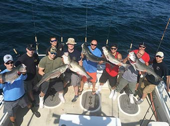 View from atop the boat looking down at nine men smiling and holding up striped bass