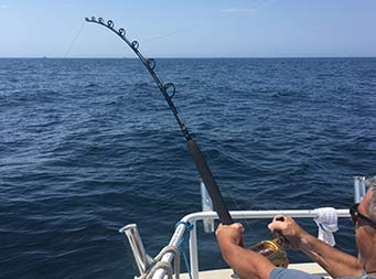 View from behind a man with his rod and line in the water reeling something in.