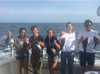 On a sunny day, 5 young adults smile and each hold up 2 sea bass.