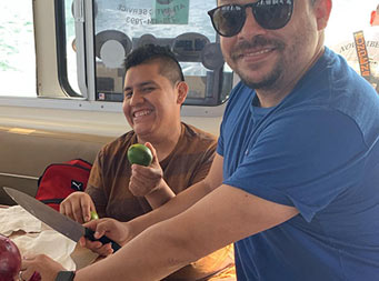 View inside the boat (in the galley) of two men preparing to make ceviche, with one man holding a whole lime, the other holding a whole red onion, and both smiling for the camera.