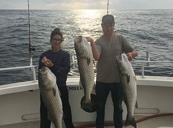 With the sun reflecting off the dark water behind them, a man holds up two striped bass and a woman holds up one.
