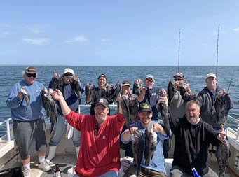A group of 10 men sit and stand posing for the camera, all holding up sea bass.