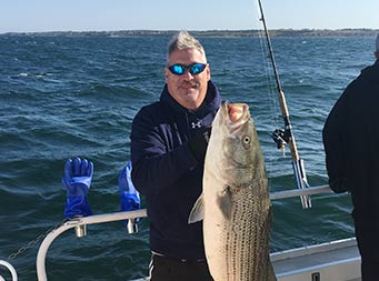 On a clear, blue-sky day, a man wearing a dark blue sweatshirt holds up a striped bass with both hands.