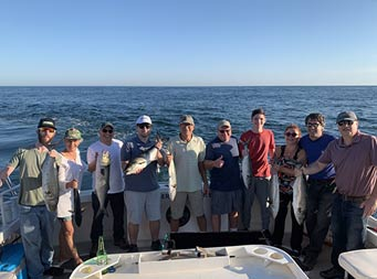 Ten men and women stand together and hold up some bluefish.