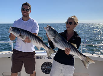 With a sunny clear blue sky above them, a man and woman, each wearing sunglasses, holds up the striped bass they caught.