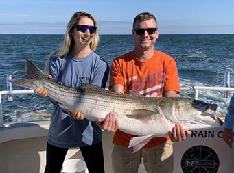 A man and woman both wearing sunglasses work together to hold up a striped bass using their arms and hands.