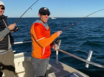 On a sunny, clear blue-sky day, a man wearing a blue hat, sunglasses and a red and orange windbreaker looks towards the camera as he holds onto his reel already in the water.