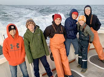 On a slightly overcast, chilly morning, 6 tween-age boys , some wearing hats and sweatshirts, pose together for a photo, with the wake of the boat behind them