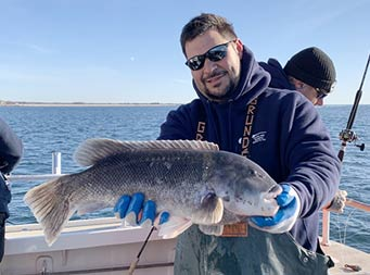 A man wearing sunglasses and a sweatshirt smiles and holds out a blackfish with two hands for the camera.