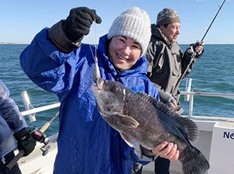 On a sunny, chilly morning, with the water behind them, a woman bundled up in a wool hat, gloves, winter coat and blue long raincoat over it, smiles big as she holds up a blackfish.