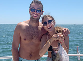 On a warm, sunny day, both wearing bathing suits, a woman holds up a large striped bass and smiles. A man stands next to her and also smiles.