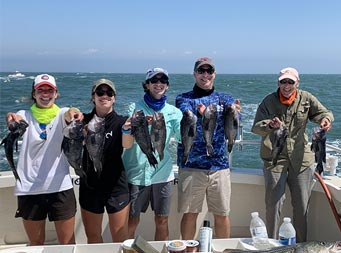 On a sunny day with mostly clear skies, three identical twins, 2 young women and 1 young man, stand with their father and grandfather, each holding up striped bass. All 5 are wearing caps and sunglasses.