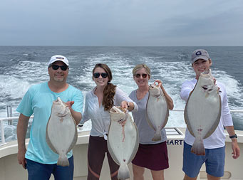 Under a Partly cloudy blue sky, two parents and two young adult son and daughter each hold up a fluke.