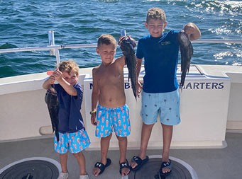 With the blue water behind them, 3 young boys, standing in size order from left to right, each hold up a sea bass.