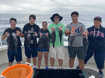 With the sky above filled with clouds and some light peeking through, two adults and 4 adolescent boys and girls stand together and each hold up 2 sea bass.