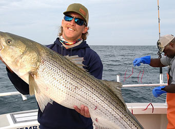 With a partly cloudy sky above, a man wearing sunglasses, holds up a large striped bass with 2 hands. First Mate Gil is seen in the background.