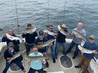 Overhead view of 1 woman and 7 men each holding a striped bass and looking up at the camera.