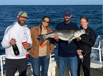 On a clear blue sky day with the water behind them, 2 men and 2 women stand together and smile holding up 1 striped bass, the man on the far left also holds up a bottle of champagne.